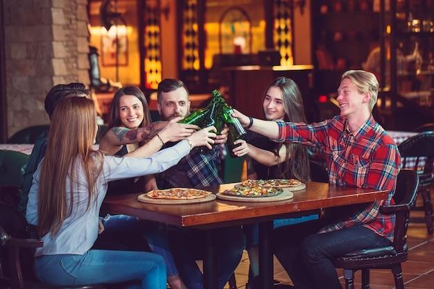 バーでドリンクを飲んでいる友人、彼らはビールとピザと木製のテーブルに座っています。 Premium写真