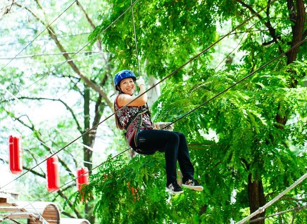 アドベンチャークライミングハイワイヤパーク-女性の登山用ヘルメットと安全装備 Premium写真