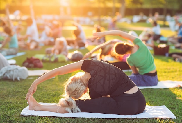若い人たちのグループは、日没時に公園でヨガをします。 Premium写真