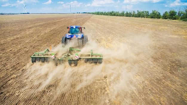 畑で耕し播種するトラクター Premium写真