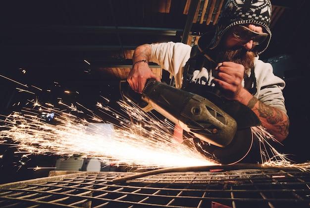 Рабочий, использующий угловую шлифовальную машину на фабрике и бросающий искры Premium Фотографии