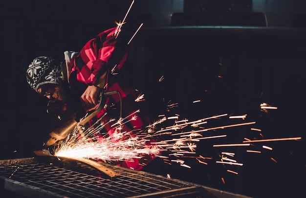 サービスステーションの従業員は、手で火花を当てる溶接機で車体修理を行います。 Premium写真