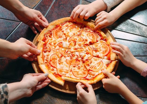 木製のテーブルからピザのスライスを取る手は、ビューを閉じます。 Premium写真