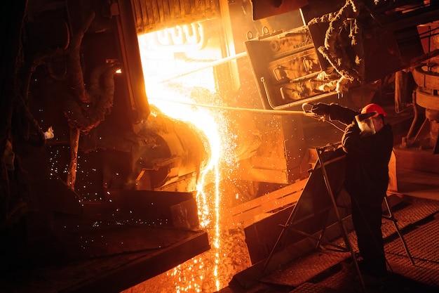 鉄鋼生産のための工場。電気溶解炉。工場労働者が金属のサンプルを採取します。 Premium写真
