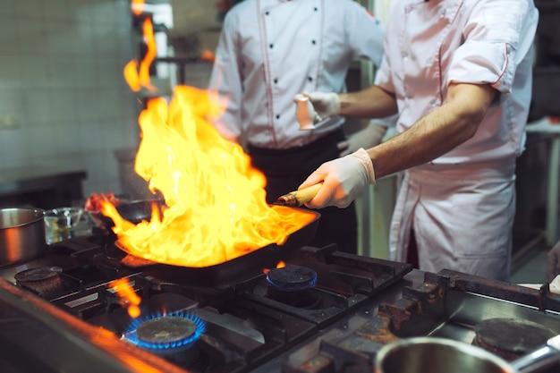 Огонь на кухне. огонь газовый ожог готовит на сковороде, очень горячий огонь Premium Фотографии
