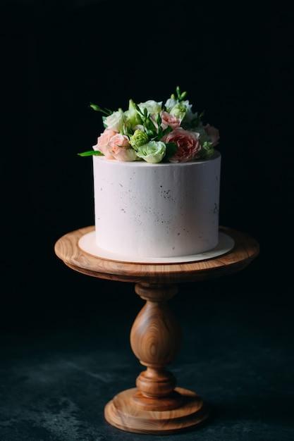 ケーキは暗いところに花で飾られています。 Premium写真