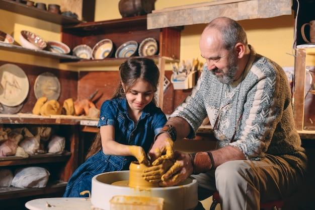 陶器のワークショップ。おじいちゃんは孫娘の陶器を教えています。粘土モデリング Premium写真