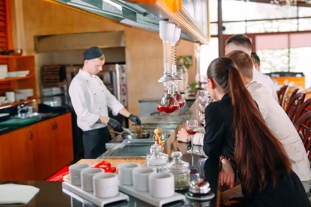 シェフがレストランの訪問者の前で食事を準備します Premium写真