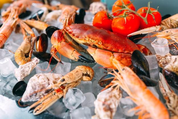 氷の上のシーフード。カニ、チョウザメ、貝、エビ、ラパナ、ドラド、白い氷の上。 Premium写真