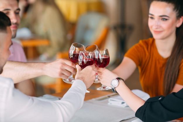 Друзья пьют вино на террасе ресторана. Premium Фотографии
