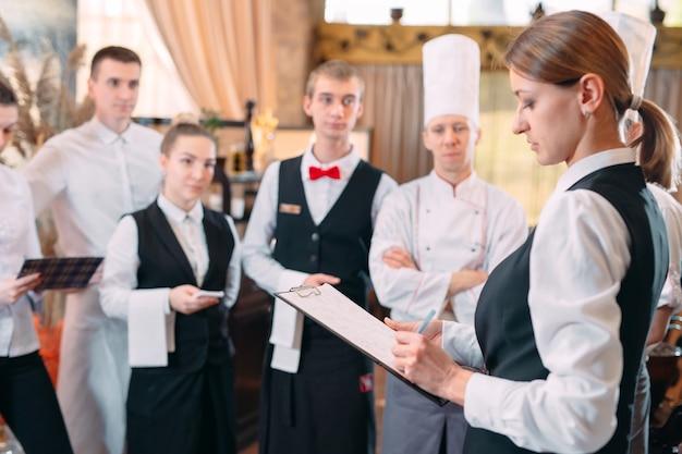 Менеджер ресторана и его сотрудники на кухне. общение с шеф-поваром на коммерческой кухне. Premium Фотографии