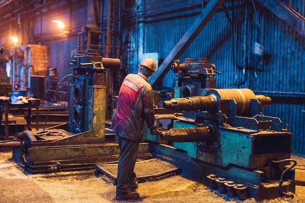重工業の労働者がマシンで一生懸命働いています。過酷な産業環境。 Premium写真