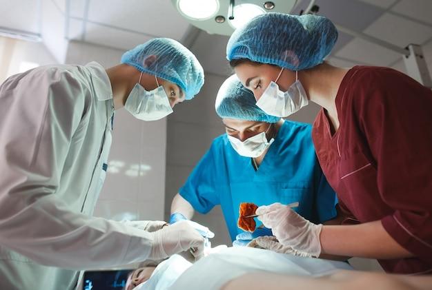手術室で手術中の外科医のグループ。蘇生医学チームは、患者を救うスチール製の医療用具を保持する保護マスクを着用しています。手術と緊急事態。 Premium写真