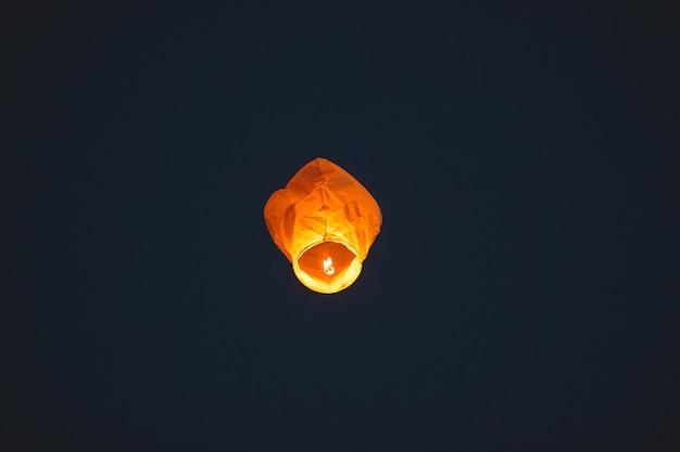 Летающий фонарь в темном небе Premium Фотографии