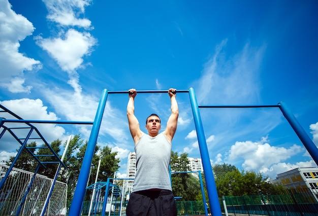 水平バーにプルアップをしている筋肉男 Premium写真