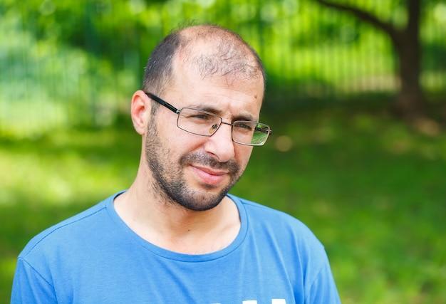 悪い視力と脱毛を持つ若い男の肖像。 Premium写真