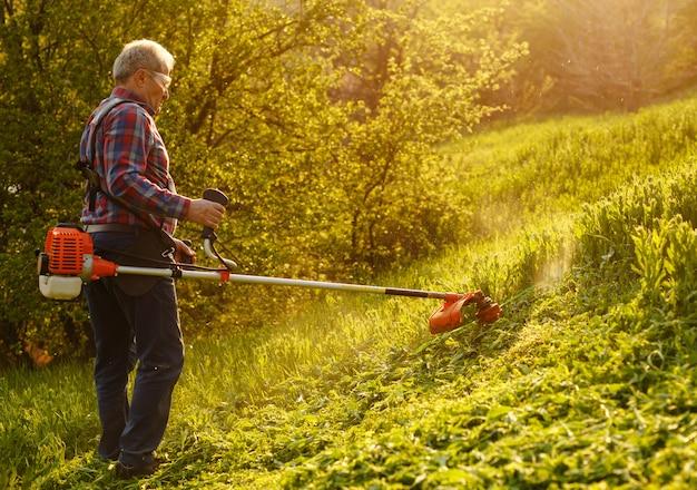 刈り取りトリマー-日没時の緑の庭で草を刈る労働者。 Premium写真