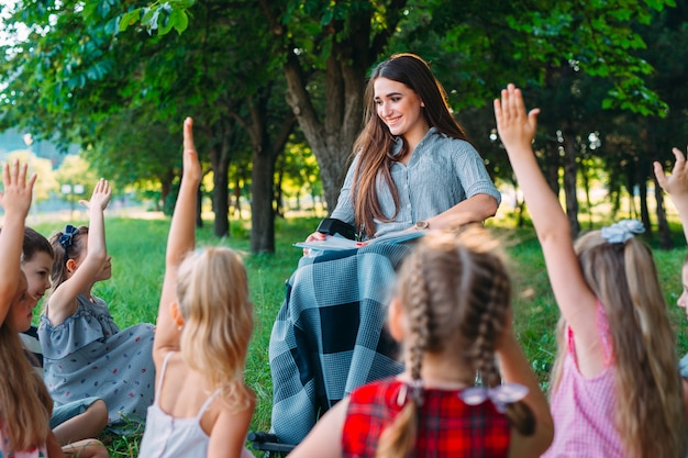 障害を持つ教師は、自然の中で子供たちとレッスンを行います。車椅子の先生と生徒の相互作用。 Premium写真