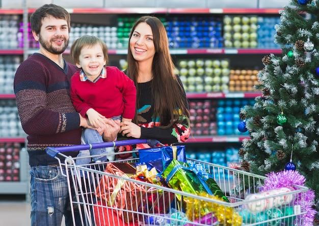 スーパーマーケットで幸せな若い家族は、新年の贈り物を選択します。 Premium写真
