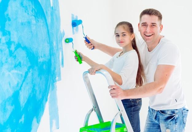 父と彼の小さな娘が新しい家で壁を塗る。 Premium写真