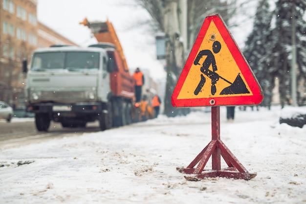 除雪車は街から雪を取り除きます。警告標識。冬季サービス車両の除雪機の作業。 Premium写真