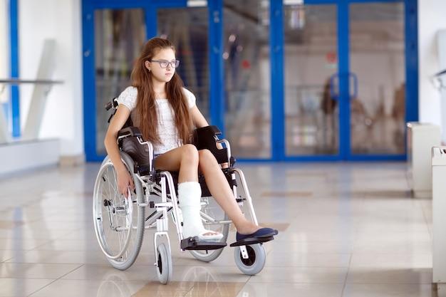 Молодая девушка в инвалидной коляске стоит в коридоре больницы. Premium Фотографии