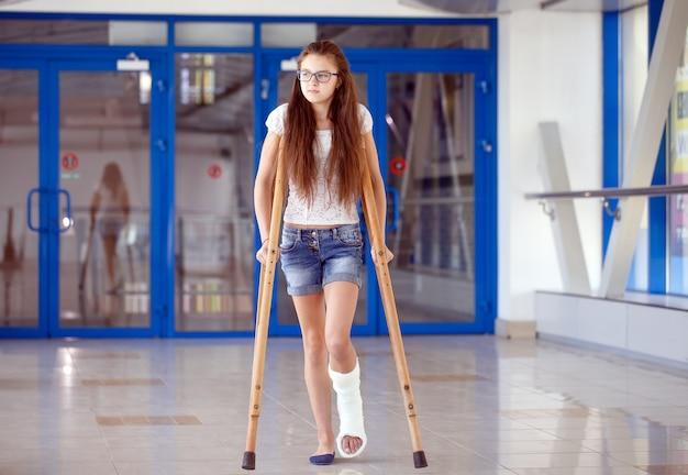 Молодая девушка на костылях в коридоре больницы. Premium Фотографии