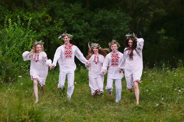 真夏、スラブの服を着て自然の中を走っている人々。 Premium写真