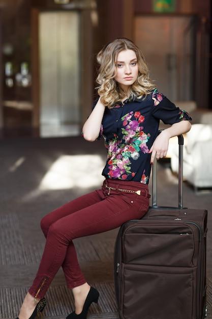 Портрет молодой женщины, сидящей на чемоданах в терминале или на вокзале, женщина познакомилась в поездке. Premium Фотографии