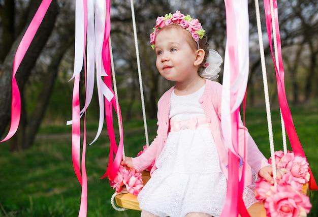 Маленькая девочка на качелях, маленькая девочка в парке Premium Фотографии