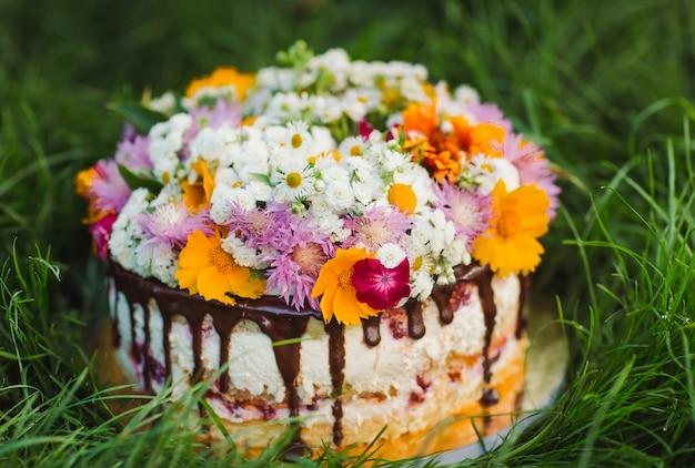 草の上の花で飾られた裸のケーキ。 Premium写真