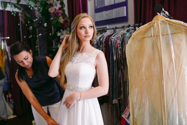 女性アシスタントの店でウェディングドレスを試着する女性。 Premium写真