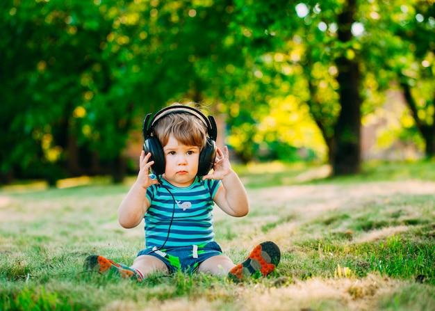 ヘッドフォンと小さな男の子。 Premium写真