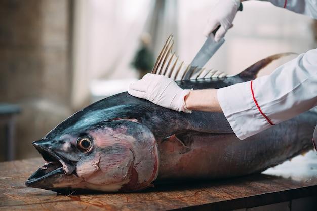 Шеф-повар разделал большую рыбу тунца в ресторане. Premium Фотографии