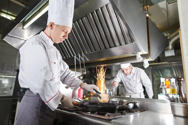 Шеф-повар в кухне ресторана на плите с кастрюлей, приготовление пищи Premium Фотографии