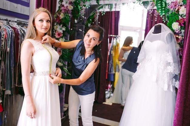 女性アシスタントとショップでウェディングドレスを試着する女性。 Premium写真