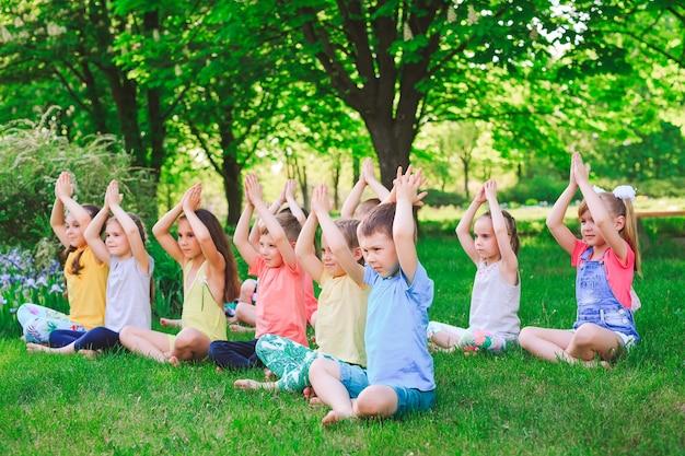 Большая группа детей занимается йогой в парке, сидя на траве. Premium Фотографии