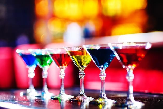 Разноцветные коктейли в баре. Premium Фотографии