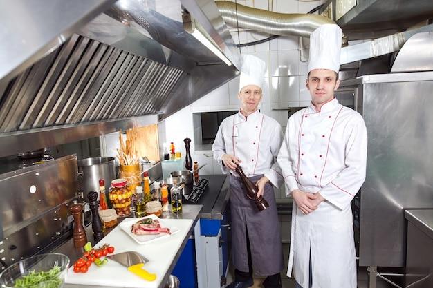 Шеф-повар готовит блюдо на кухне от ресторана. Premium Фотографии