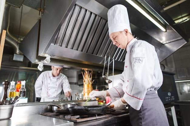 Шеф-повар на кухне ресторана в печи с кастрюлей, приготовление пищи Premium Фотографии