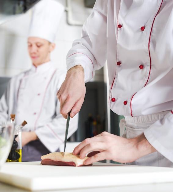 Шеф-повар режет мясо на разделочной доске, профессиональный повар держит нож и нарезает мясо в ресторане Premium Фотографии