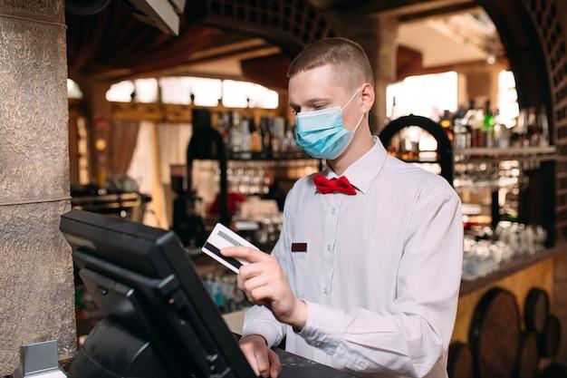 Малый бизнес, люди и концепция обслуживания. человек или официант в медицинской маске на прилавке с кассы, работающие в баре или кафе. Premium Фотографии