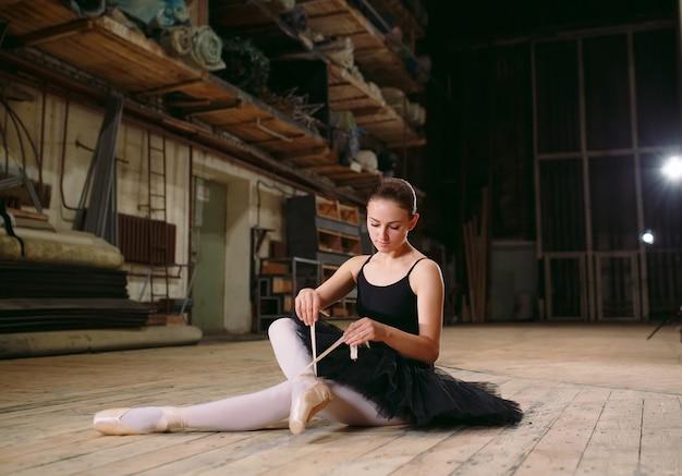 黒のドレスを着た若いバレリーナが舞台裏で電車に乗っています。 Premium写真