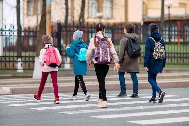 Школьники переходят дорогу в медицинских масках. дети ходят в школу. Premium Фотографии