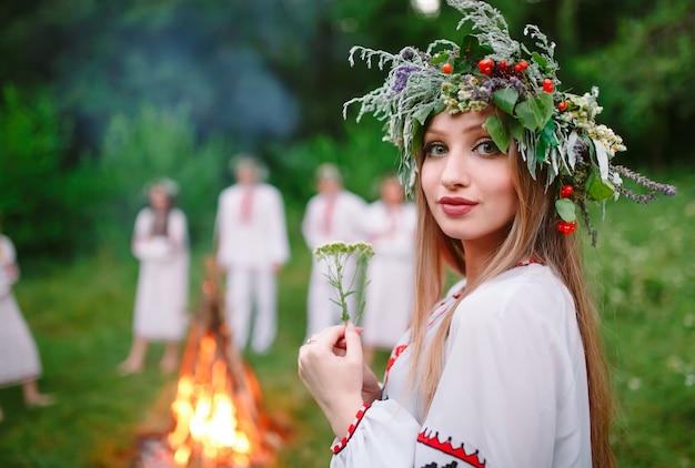 真夏。火の近くのスラブの服の美しい少女の肖像画。 Premium写真