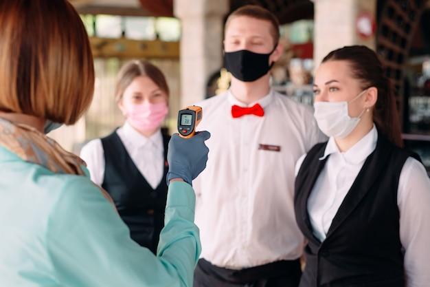 レストランやホテルのマネージャーは、熱画像装置でスタッフの体温をチェックします。 Premium写真