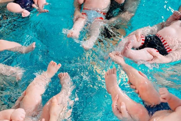 Группа матерей с маленькими детьми на уроке детского плавания с тренером. Premium Фотографии
