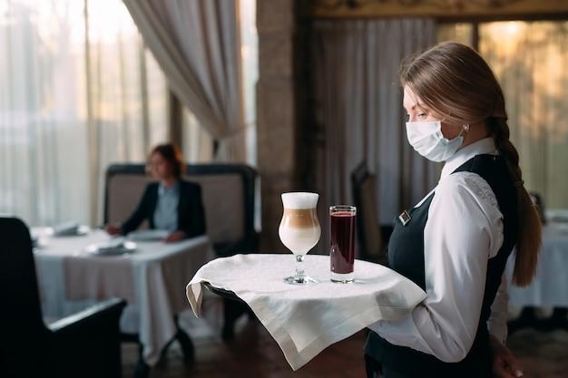 Официантка европейской внешности в медицинской маске подает кофе латте. Premium Фотографии