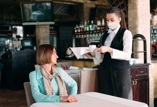 По-европейски выглядящий официант в медицинской маске подает кофе. Premium Фотографии