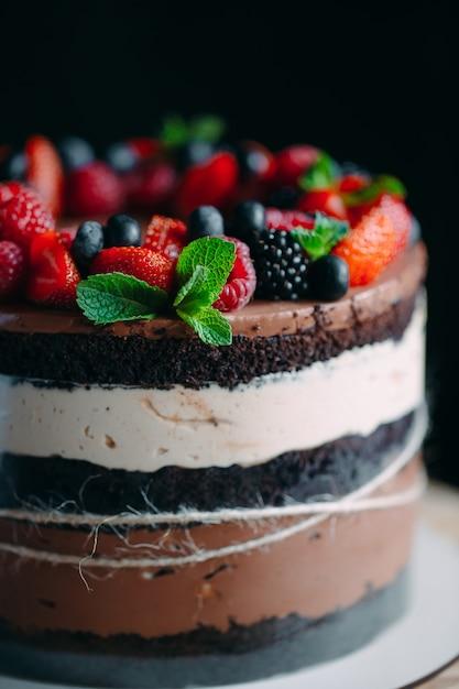 Фруктовый торт торт украшенный ягодами на деревянной подставке на черном Premium Фотографии